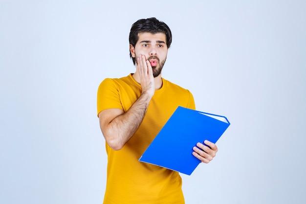 Mężczyzna z niebieską teczką wygląda na zdezorientowanego lub niedoświadczonego.