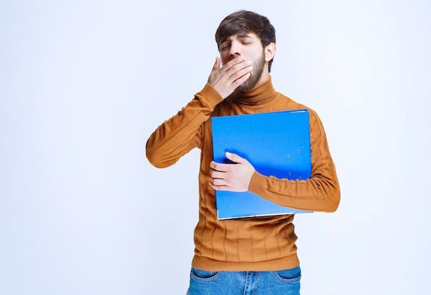 Mężczyzna z niebieską teczką wygląda na zmęczonego i sennego.