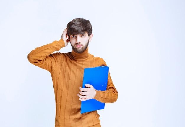 Mężczyzna z niebieską teczką wygląda na zmieszanego i przerażonego.