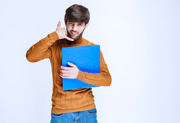 Mężczyzna z niebieską teczką z prośbą o telefon.
