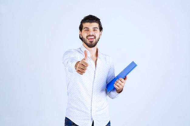 Mężczyzna z niebieską teczką ze znakiem przyjemności