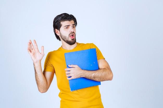 Mężczyzna z niebieskim folderem wygląda na zdezorientowanego