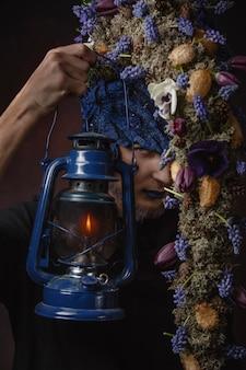 Mężczyzna z niebieskimi kwiatami i lampą w ciemnym pokoju