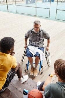 Mężczyzna z niepełnosprawnością rozmawia ze sportowcami