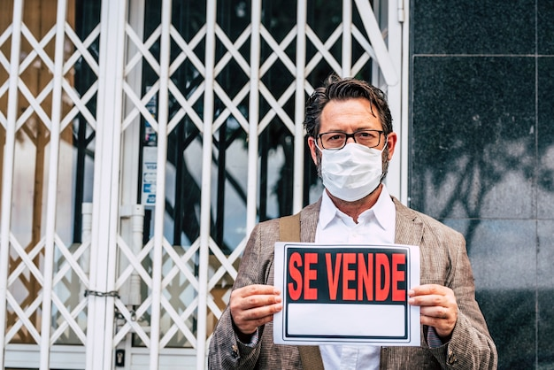 Mężczyzna z nieudanym sklepem biznesowym ze znakiem wyprzedaży poza swoim sklepem w masce ochronnej przed wirusem