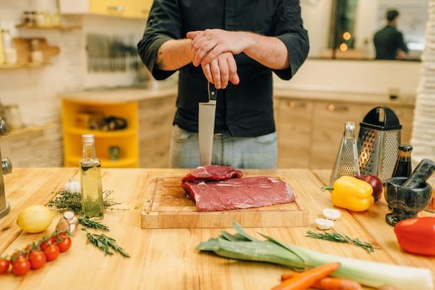 Mężczyzna z nożem i kawałkiem surowego mięsa