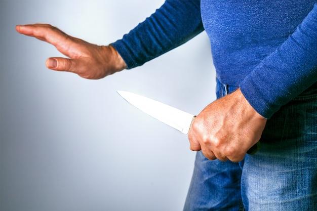 Mężczyzna z nożem i ręką w geście pojednania. koncepcja zagrożenia konfliktem.