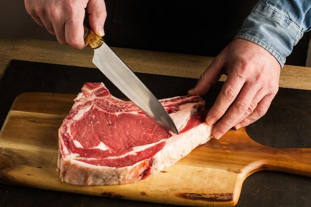 Mężczyzna z nożem w ręku i stek z cielęciny na drewnianej desce kuchennej