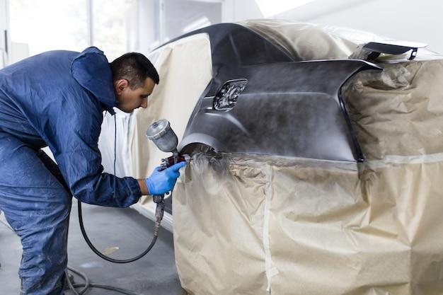 Mężczyzna z odzieżą ochronną i maską do malowania samochodu za pomocą sprężarki w sprayu. selektywne skupienie.