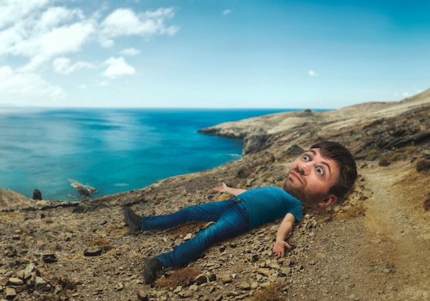Mężczyzna z ogromną głową leżący na wybrzeżu morza