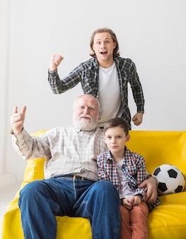 Mężczyzna z ojcem i synem ogląda mecz futbolowego