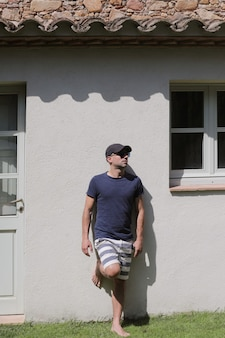 Mężczyzna z okularami przeciwsłonecznymi i kostiumem kąpielowym, opierając się na ścianie na zewnątrz