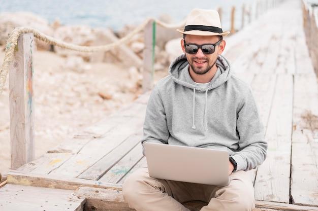 Mężczyzna z okularami przeciwsłonecznymi pracuje na laptopie przy plażą