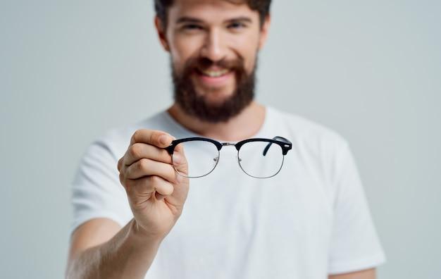 Mężczyzna z okularami w dłoni problemy ze wzrokiem ból oczu krótkowzroczność soczewki nadwzroczności