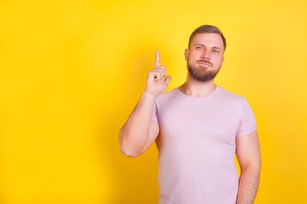 Mężczyzna z palcem wskazującym uniesionym na żółtym tle, na prawo od miejsca na tekst, z miejscem na kopię. koncepcja jest ważnym pomysłem, wyborem lub decyzją, ważną informacją.