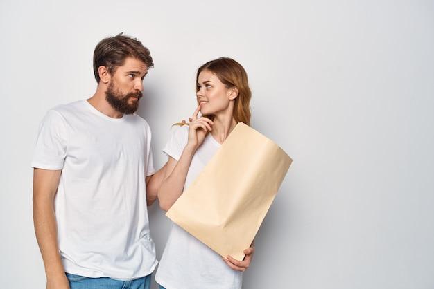 Mężczyzna z papierową torbą obok kobiety robi zakupy rodzinne emocje