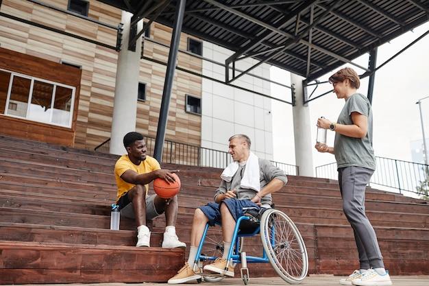Mężczyzna z paraplegią rozmawia ze sportowcem po meczu