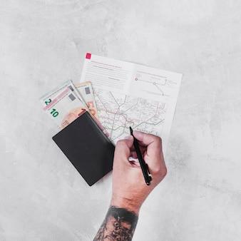 Mężczyzna z paszportem i euro notuje ocechowanie na drogowej mapie