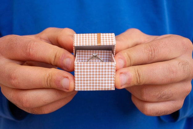 Mężczyzna z pierścionkiem w małym pudełeczku w rękach proponuje się ożenić.