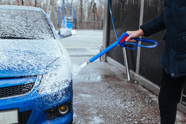 Mężczyzna z pistoletem do nakładania pianki na samochód. myjnia samoobsługowa