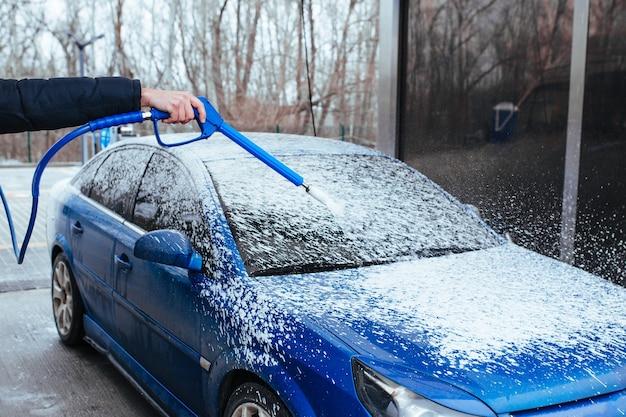 Mężczyzna z pistoletem do nakładania piany na samochód. myjnia samoobsługowa