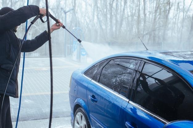 Mężczyzna z pistoletem myje samochód. myjnia samoobsługowa