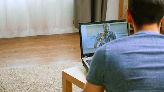 Mężczyzna z piwem podczas rozmowy wideo z jednym ze swoich przyjaciół podczas globalnej izolacji.