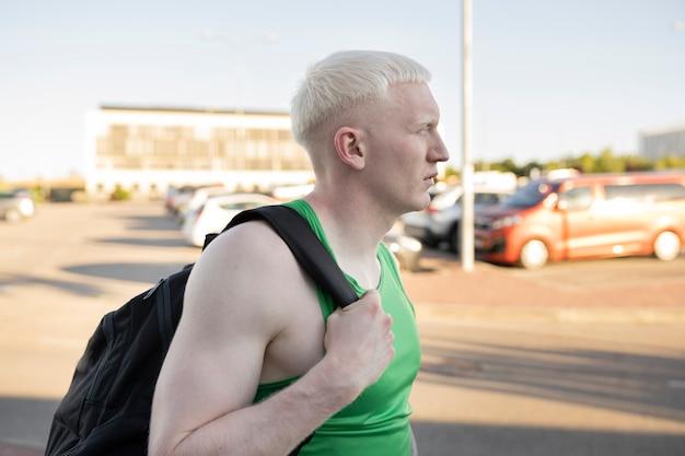 Mężczyzna z plecakiem idzie na siłownię