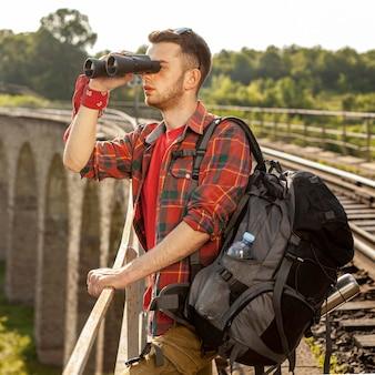 Mężczyzna z plecakiem na moście patrząc przez lornetkę
