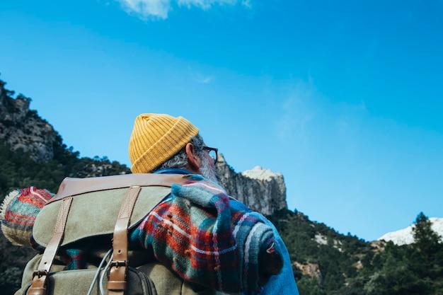 Mężczyzna z plecakiem na wędrówki po górach. słoneczna pogoda na wiosnę.