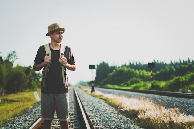 Mężczyzna z plecakiem odchodzącym na linii kolejowej i kładący nacisk na cierpliwość i ankietę próbuje krok do przodu.