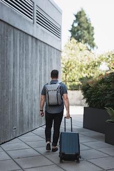 Mężczyzna z plecakiem prowadzącym walizkę