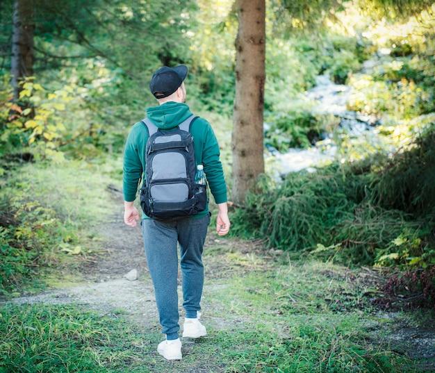 Mężczyzna z plecakiem spaceruje po jesiennym lesie. samotne wędrówki po jesiennych leśnych ścieżkach. koncepcja podróży.