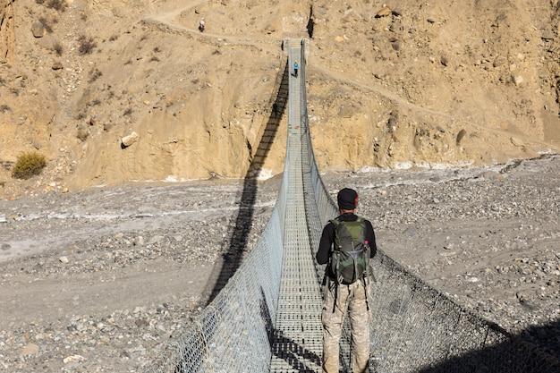 Mężczyzna z plecakiem stoi na wiszącym kładce dla pieszych nad górskim wąwozem i patrzy na góry