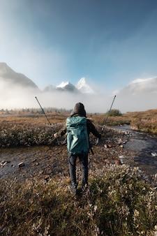 Mężczyzna z plecakiem stojący i podnoszący kijki trekkingowe na jesiennym polu w mglistych górach skalistych