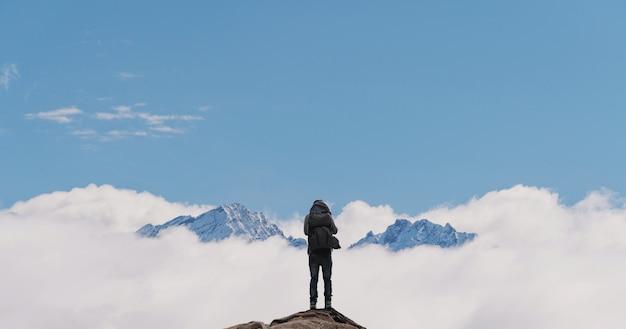 Mężczyzna z plecakiem stojący samotnie na szczycie góry
