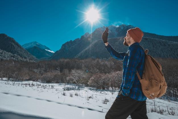 Mężczyzna z plecakiem trekking w górach. zimna pogoda, śnieg na wzgórzach. zimowe wędrówki. słońce i śnieg
