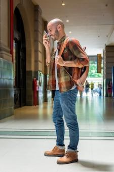 Mężczyzna z plecakiem używać wiszącą ozdobę