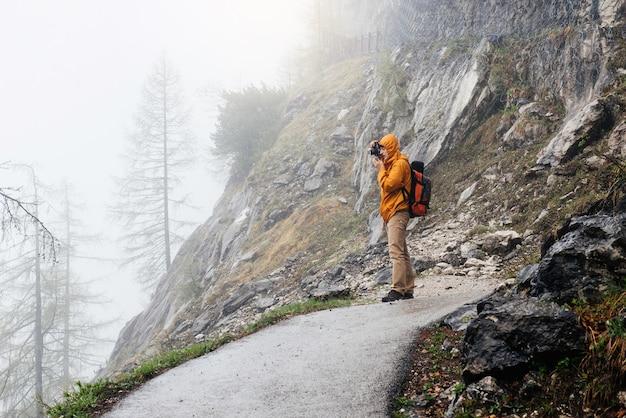 Mężczyzna z plecakiem wędruje w mglistych górach skalistych