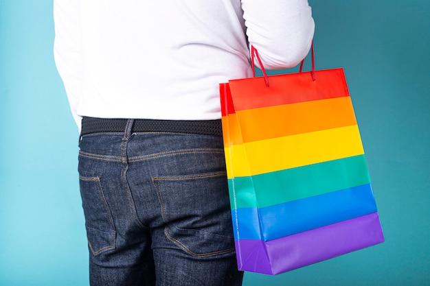 Mężczyzna z plecami do kamery na sobie niebieskie dżinsy i torbę z kolorami lgtb na niebieskim tle.