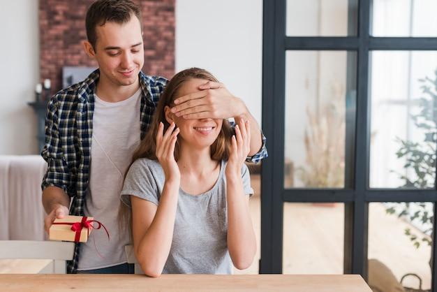 Mężczyzna z prezentem zamykając oczy kobiety