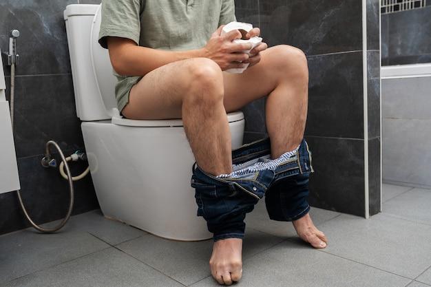 Mężczyzna z problemami żołądkowymi siedzi w muszli klozetowej i trzyma rolkę z chusteczkami w łazience