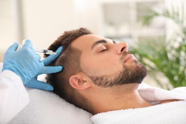 Mężczyzna z problemem wypadania włosów otrzymujący zastrzyk w klinice