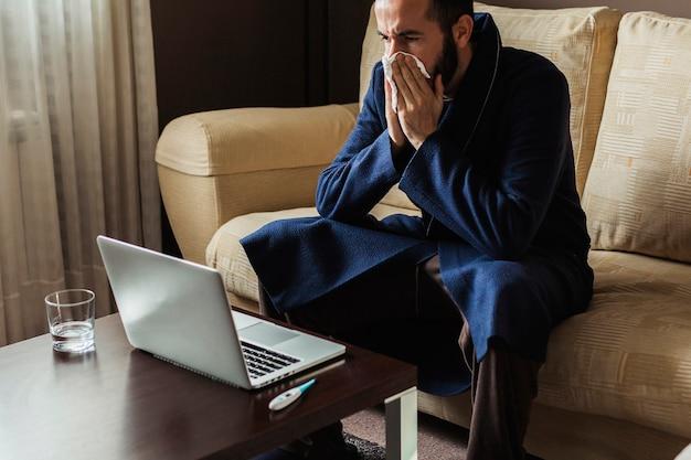 Mężczyzna z przeziębieniem robi z domu konsultację lekarską online ze swoim lekarzem