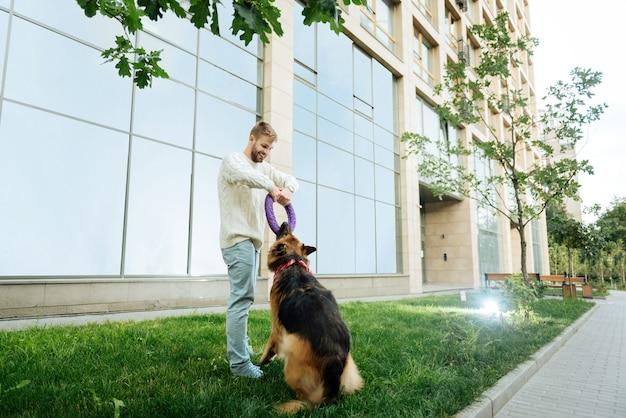 Mężczyzna z psem. młody blondyn czuje się szczęśliwy i zabawiony podczas zabawy z psem w pobliżu swojego domu