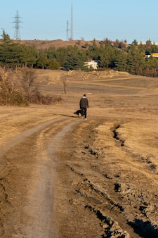 Mężczyzna z psem na polnej drodze do samochodów