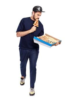 Mężczyzna z pudełkiem pizzy w rękach zjada kawałek. facet w czapce i niebieskim ubraniu. dostawa jedzenia. pełna wysokość. na białym tle. pionowy.