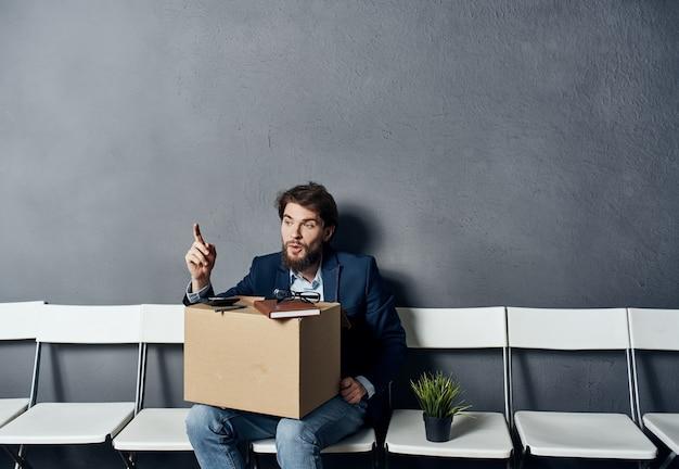 Mężczyzna z pudełkiem siedzi na krześle z rzeczami i dokumentami po zwolnieniu