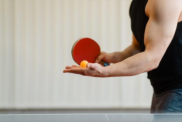Mężczyzna z rakietą do ping-ponga przygotowuje się do uderzenia piłki