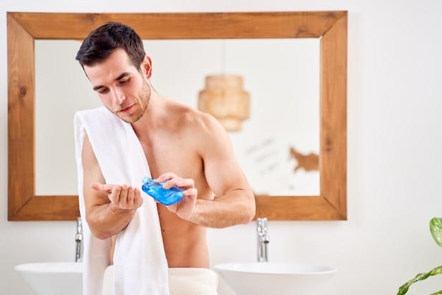Mężczyzna z ręcznikiem na ramionach z balsamem w dłoni stoi przed lustrem w łazience